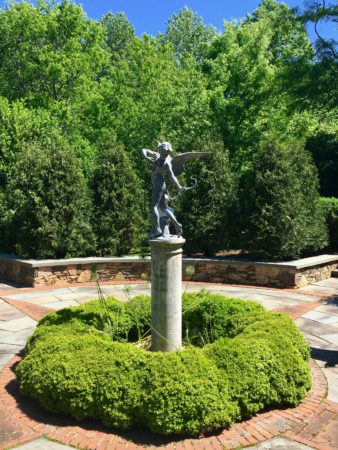 Eros statue surrounded by boxwood/Here By Design