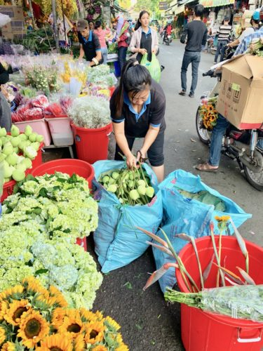 Vendor opening deliveries at Ho Thi Ky flower market